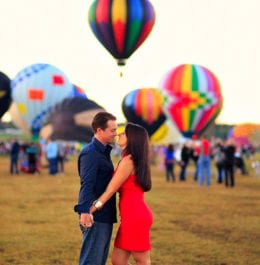 Couple standing together in front of hot air balloons