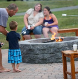 Family sitting around a fire roasting S'mores